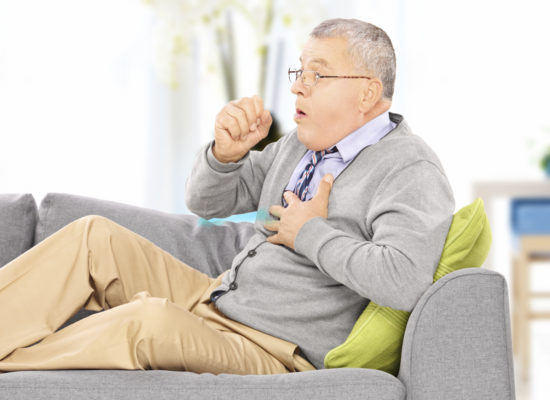 Mature man seated on a sofa coughing because of pulmonary disease at home